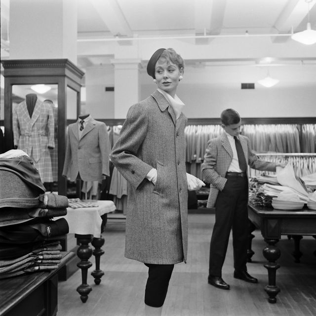 subject woman wearing long coat with hat and gloves while shopping in a brooks brothers department store while young boy shops through a pile of button down dress shirts new york, ny march 1954nphoto by nina leenthe life picture collection via getty images