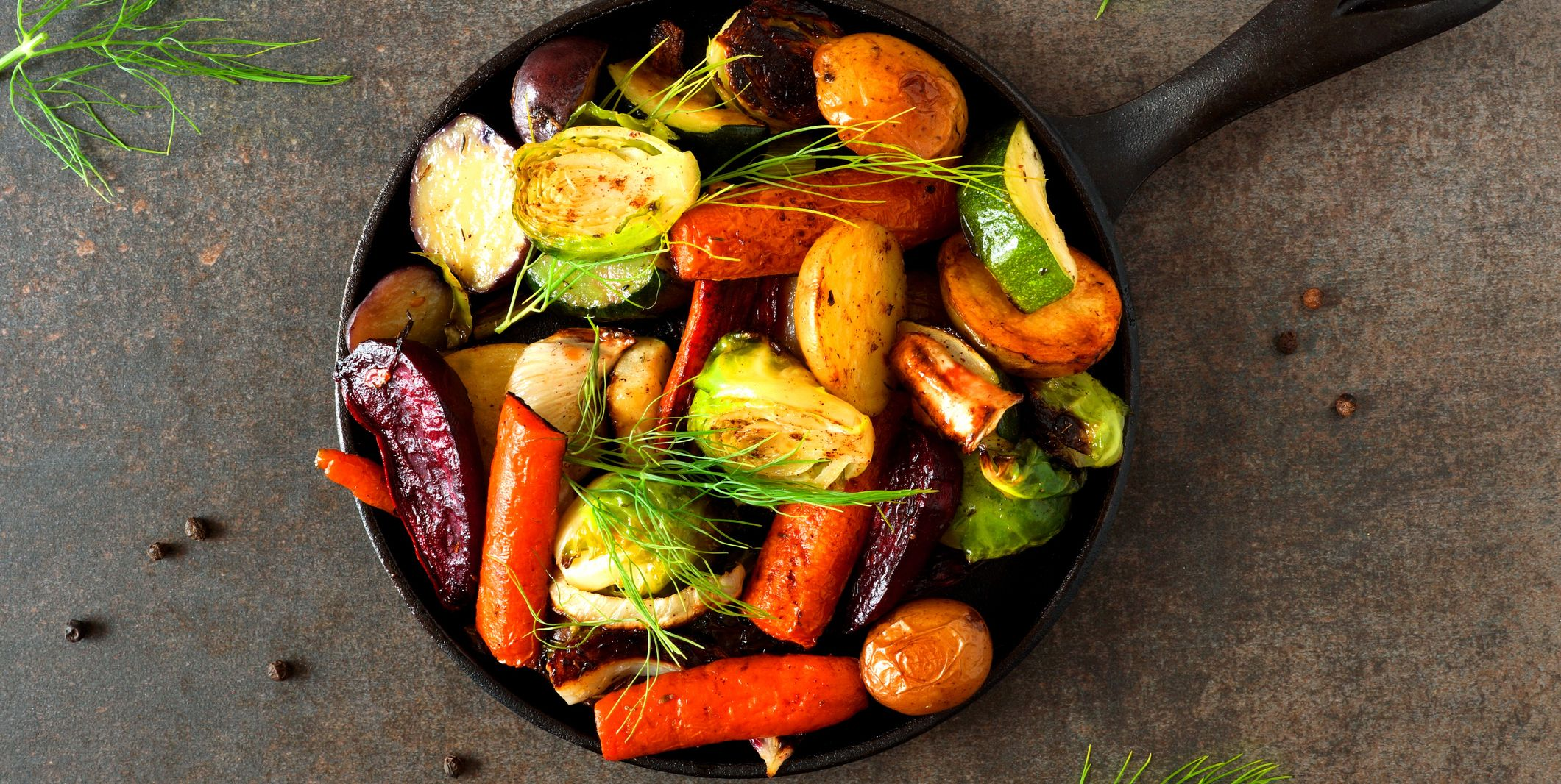 Skillet of roasted vegetables, above view on dark stone