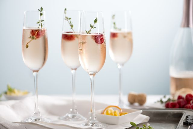 flutes of pink rose champagne garnished with red raspberries and green thyme make for a festive cocktail gathering