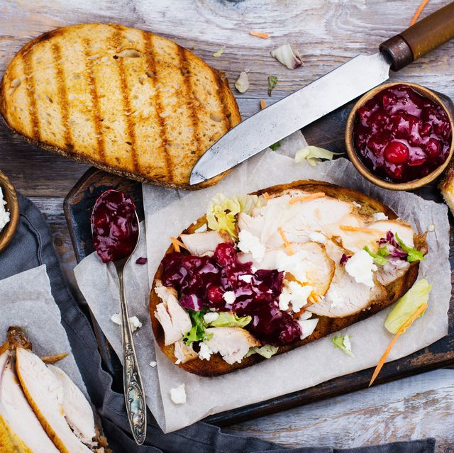homemade leftover thanksgiving day sandwich with turkey, cranberry sauce, feta cheese and vegetables top view