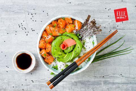 Hawaiian salmon poke bowl with seaweed, avocado rose, sesame seeds and scallions. Top view, overhead, flat lay, copy space