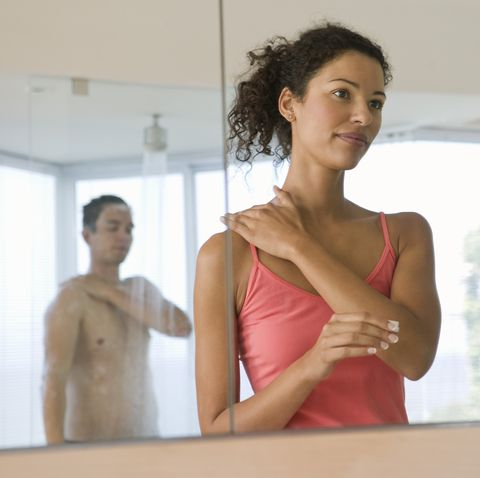 Couple getting ready in bathroom mirror