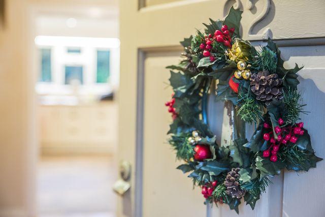 christmas wreath hung on front door with door ajar