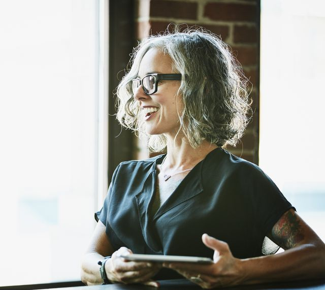 smiling businesswoman with digital tablet listening during meeting in office