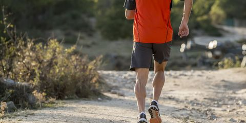 runner sport man with ripped athletic and muscular legs running uphill off road in jogging training workout at countryside in Autumn background in fitness concept