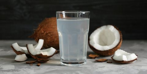glass of coconut water and fresh nuts on dark background