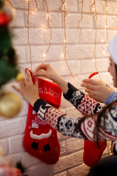 rear view of romantic happy young love couple with santa hats and sweaters decorating wall together with christmas socks for holidays