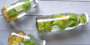 Three bottles of infused water with basil, physalis and sweet lime