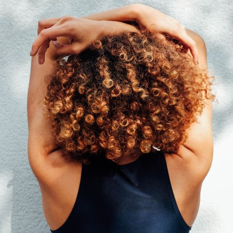 rear view of woman with curly hair against wall