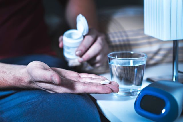 man's hand holding pill, man sitting on bed