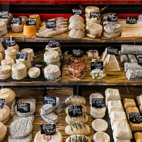 A large selection of different French and Italian cheeses on the counter of a small shop in the Aligre Market Marche Daligre in the Bastille District of Paris, France