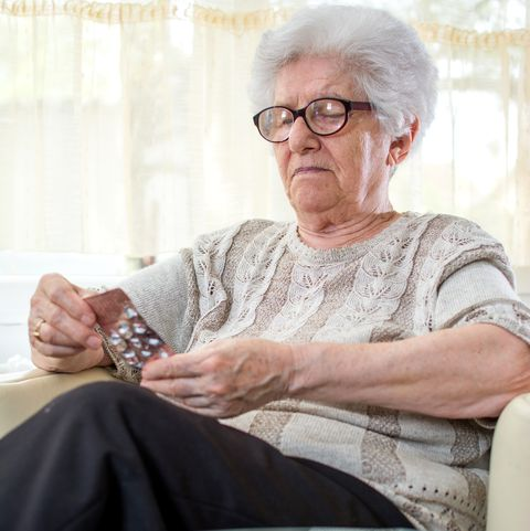 Serious senior woman in eyeglasses reading pill labels at home.