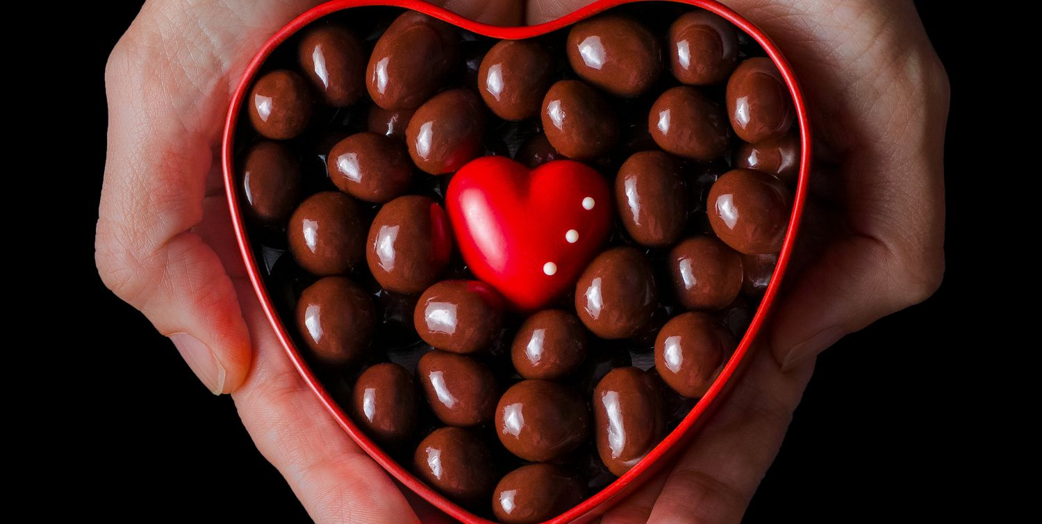 Human hands holding red heart shaped box full of chocolate