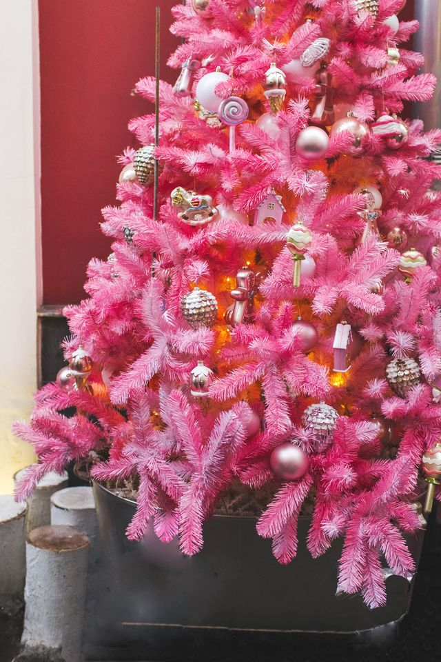 unusual artificial christmas tree decoration on pink fir branches, cute glass handmade toys new year decor