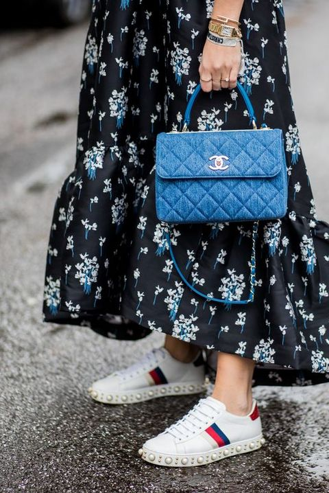 hamburg, germany   december 05 aylin koenig wearing white gucci sneakers, blue chanel bag, a navy dress with floral print hm x erdem, a black hoody asos, black gucci belt, ray ban sunglasses on december 5, 2017 in hamburg, germany photo by christian vieriggetty images