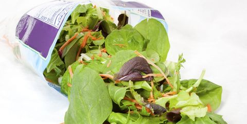Close up of contents of open bag of salad. Lettuce and carrots. Deep focus. White background. Horizontal.