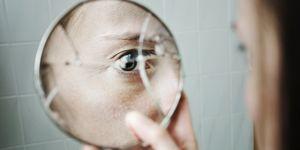 Woman looking at broken mirror