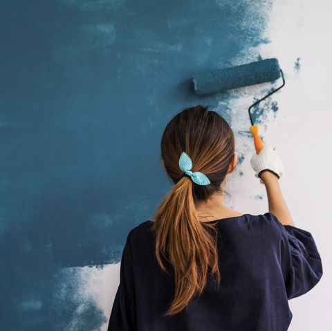 Young asian happy woman painting interior wal