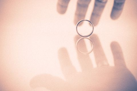 hand taking a wedding  ring reflected on a surface retro style