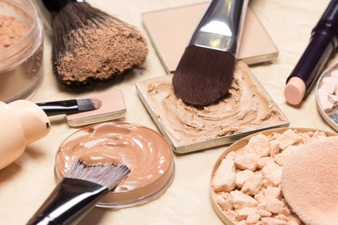 foundation, powder, concealer with make up brushes on crumpled paper corrective makeup products and accessories close up, selective focus