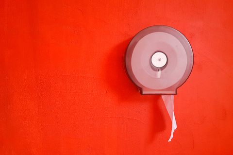 Toilet paper roll on red wall