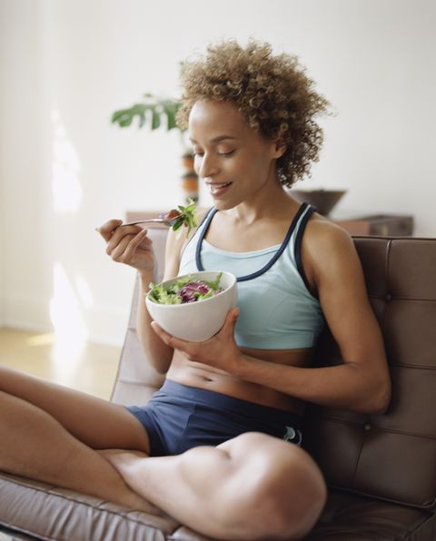 Seated woman eating salad