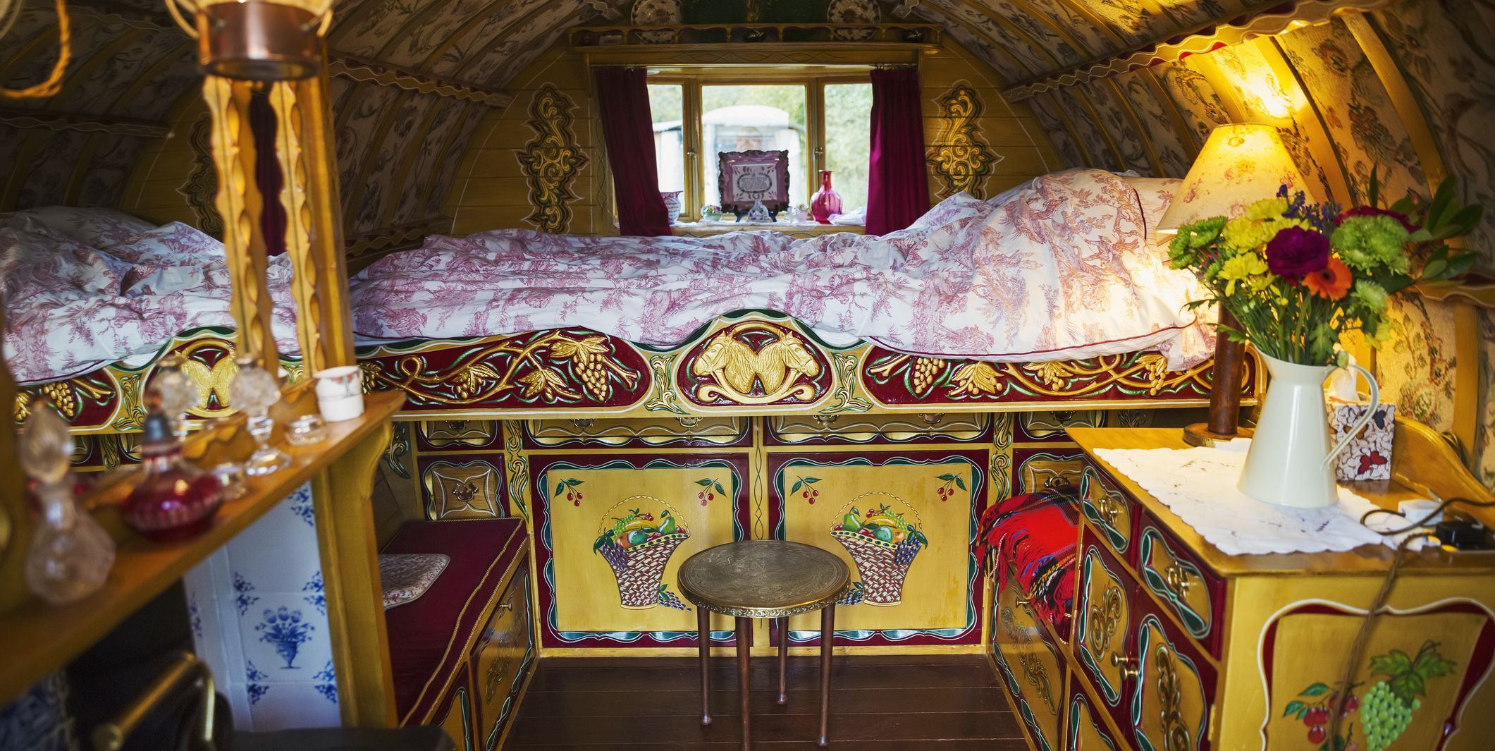 The interior of a traditional gypsy caravan with raised bed and cupboards, bow top roof and stove.