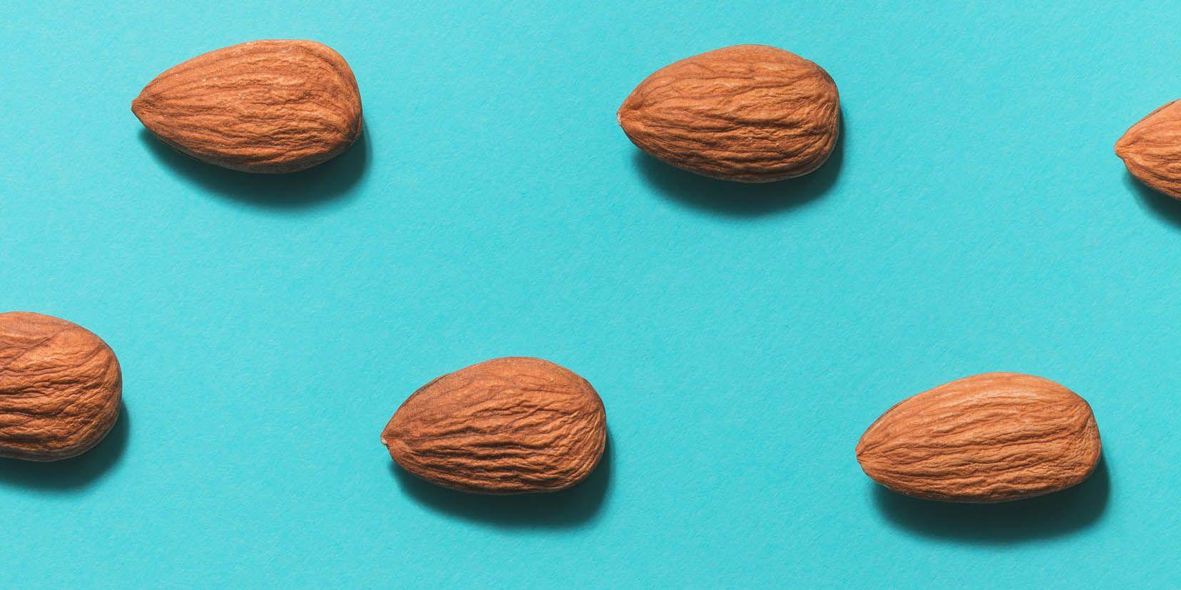 Symmetrical pattern of almonds on blue. Flat lay.