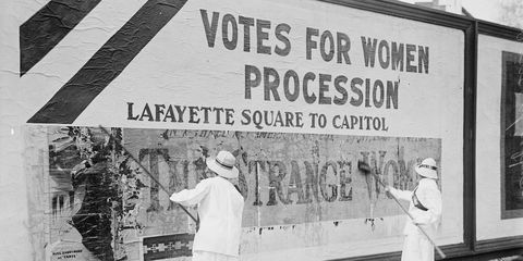 """Suffragettes uses Long Brushes to Post a Billboard announcing a """"Votes"""" For Women"""" Parade"""