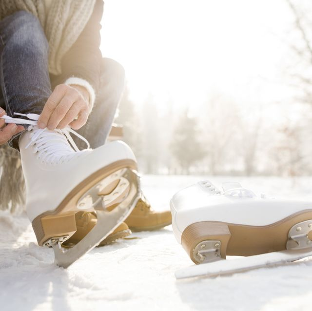 Woman sitting on bench in winter landscape putting on ice skates