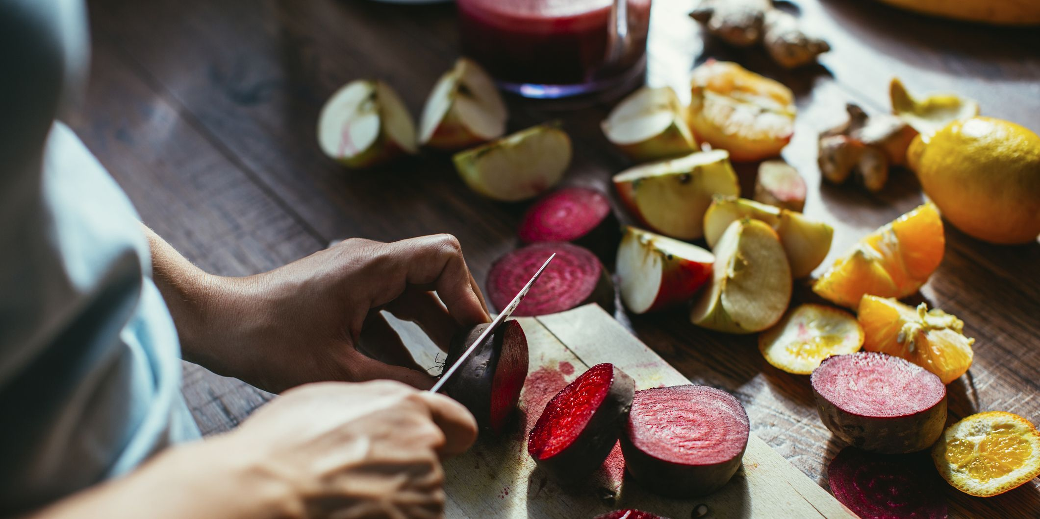 Womans hands chopping beetroot for squeezing juice
