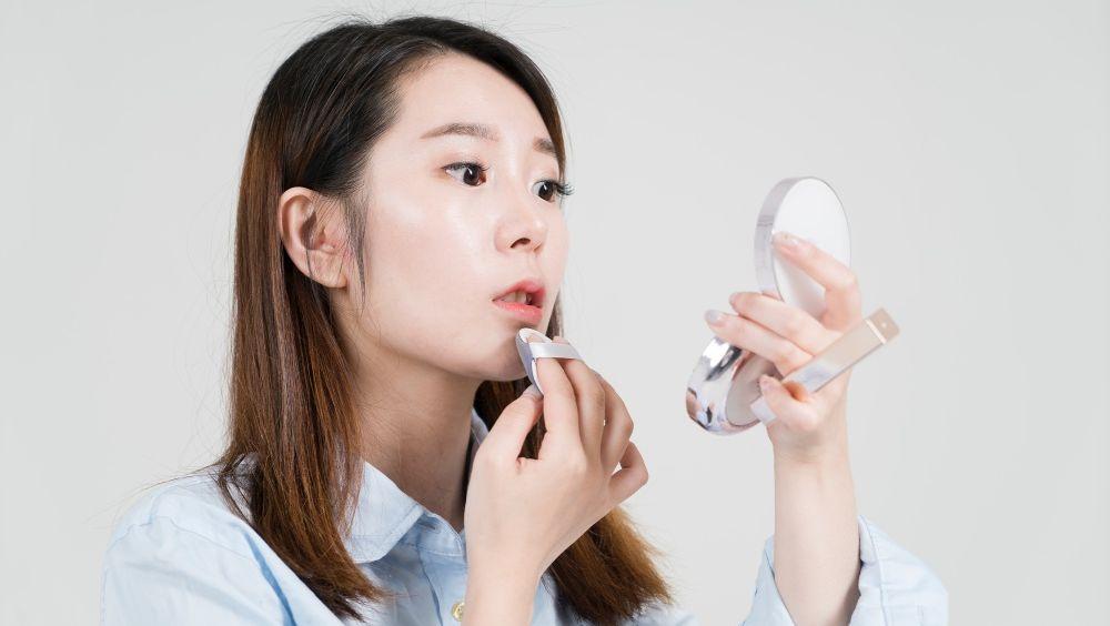 studio shot of young asian businesswoman applying makeup