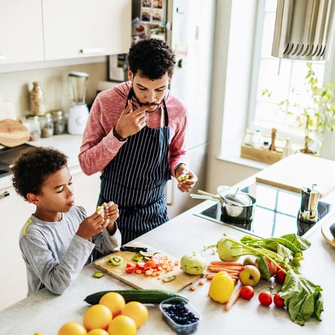 Single Dad Snacking With His Son While Preparing Lunch
