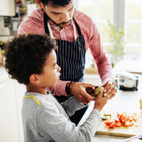 a father is carefully showing his son how to peel fruit and chop vegetables at home in the kitchen
