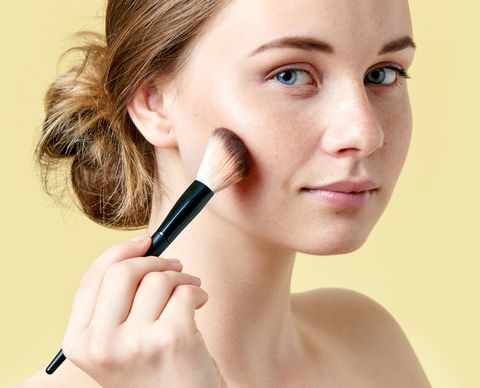 beautiful young redhead woman with freckles contouring her cheekbones using make up brush beauty portrait on yellow background