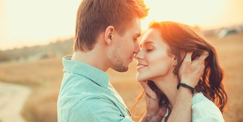 Young couple in love outdoor.in summer in field. Couple hugging. Young beautiful couple in love staying and kissing on the field on sunset. Soft sunny colors.