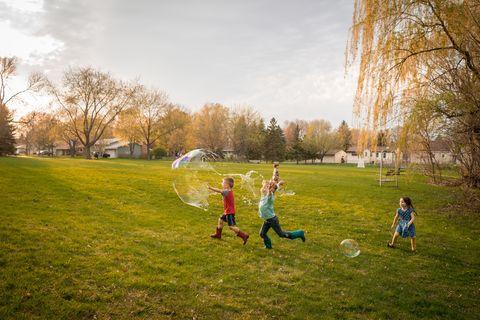four children chasing giant soap bubbles in a public park