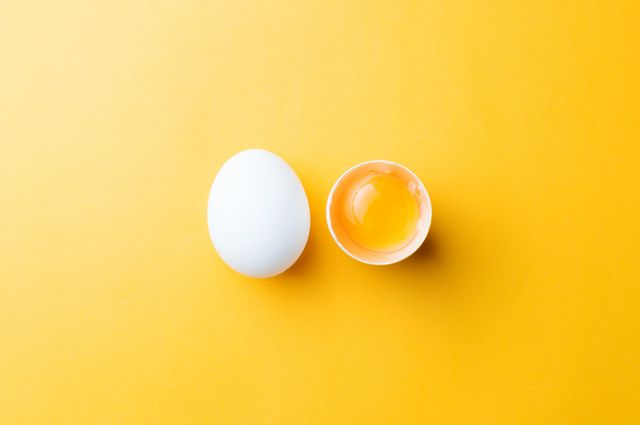 white egg and egg yolk on the yellow background
