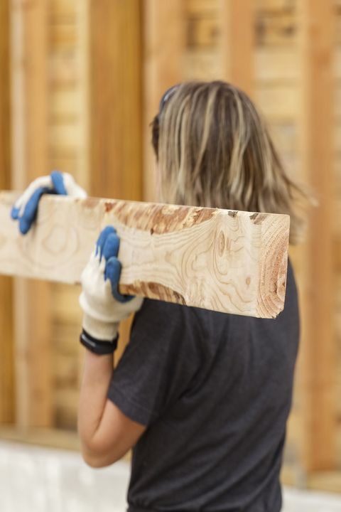 Caucasian woman carrying lumber at construction site