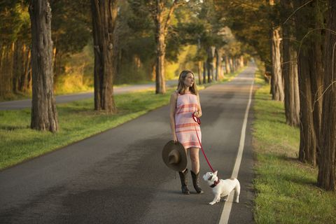 Caucasian woman holding a cowboy hat walking dog