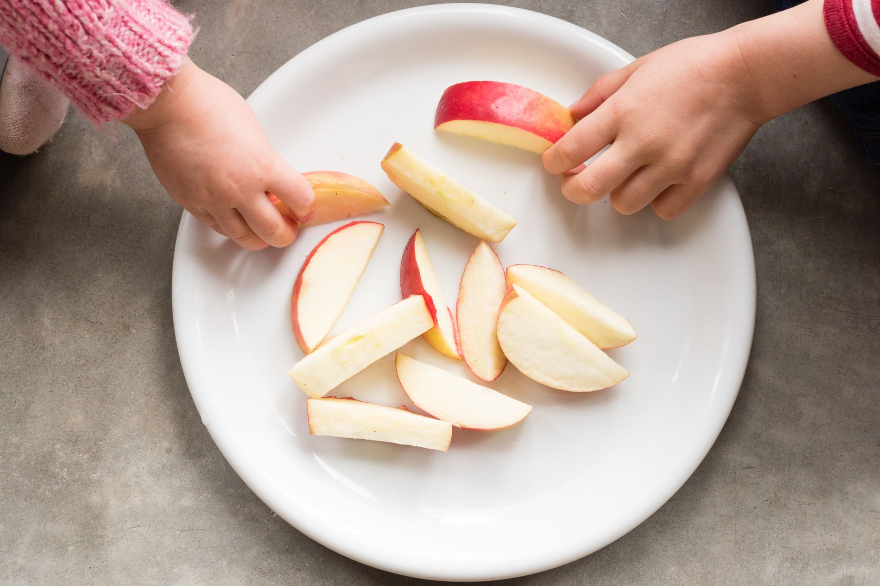 Cropped Hands Of Children Having Apple At Home