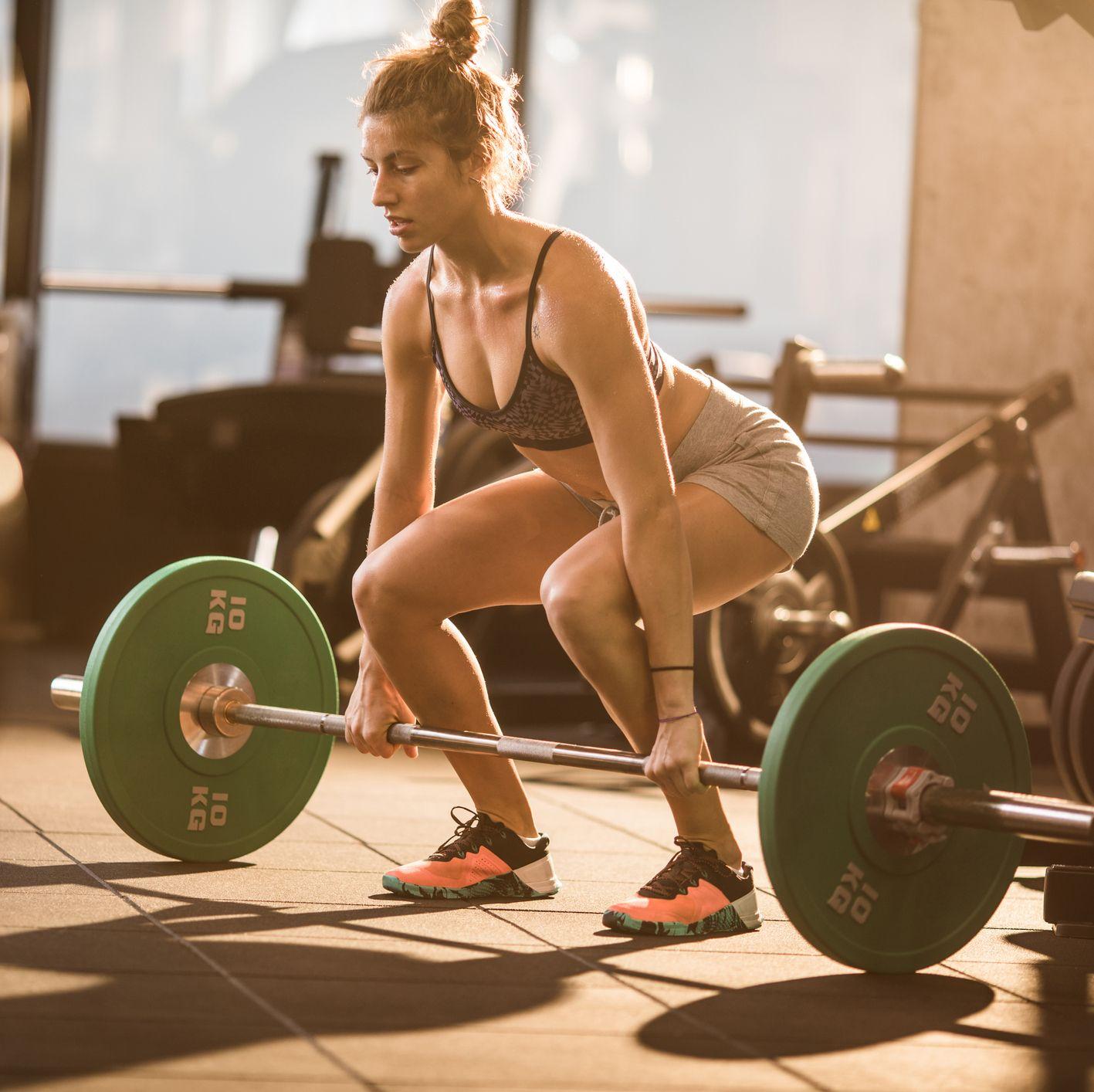Female athlete preparing for a deadlift in a health club.