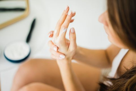 Woman creaming her hands, partial view