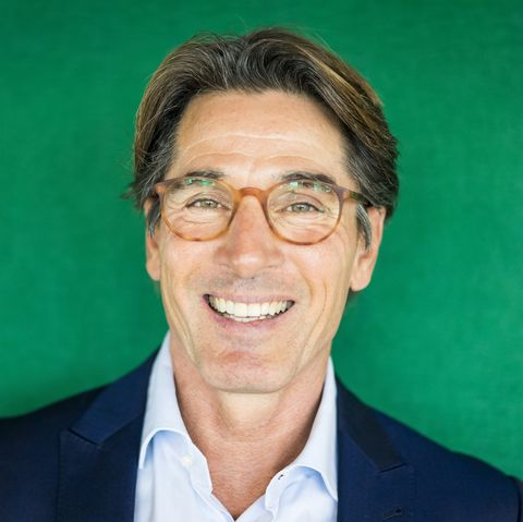 Portrait of smiling businessman with glasses in front of green wall