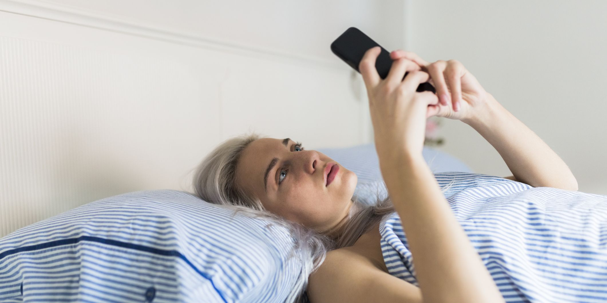 Serious young woman lying in bed checking cell phone