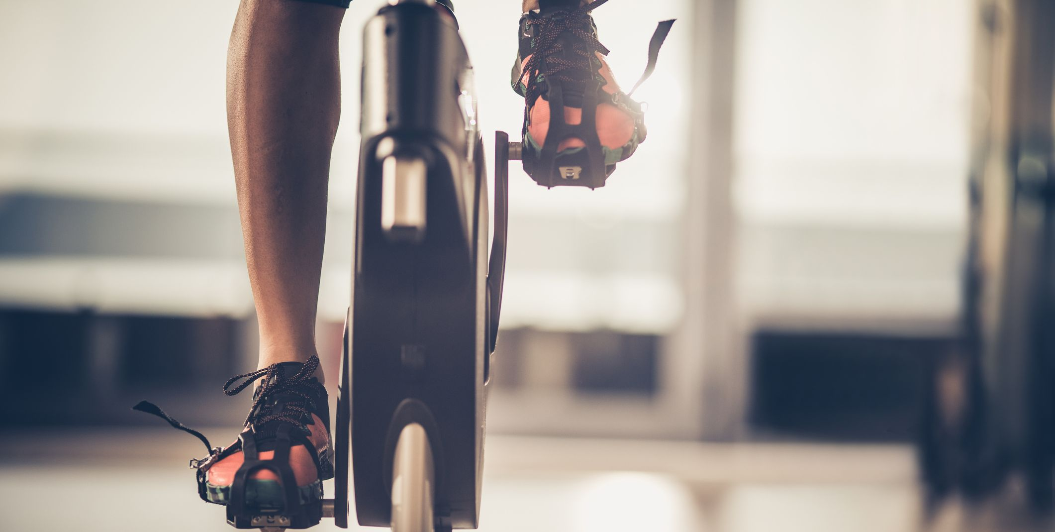 Unrecognizable athlete cycling on stationary bike in a health club.