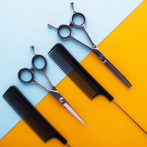 combs and hairdresser tools on color cardboard background top view