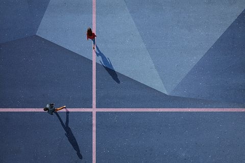 Top view of two people walking in each direction on painted asphalt