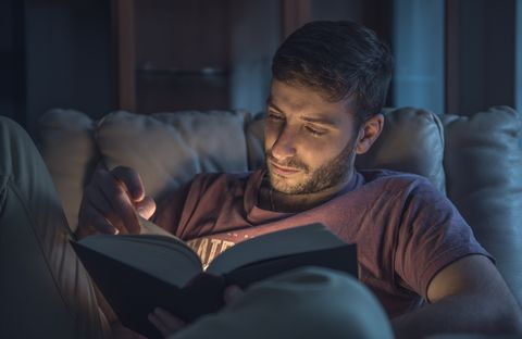 Close-Up Of Man Reading Book While Sitting On Sofa At Home