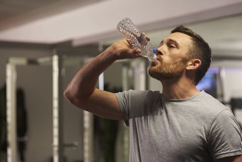 Man in gym drinking water.